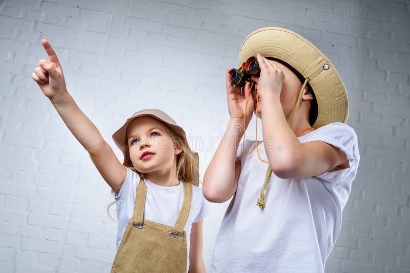 crianças em trajes e em chapéus do safari que apontam e que olham imagem de stock