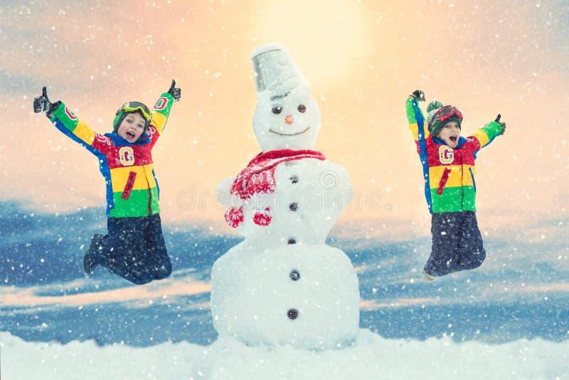 Crianças em um molde nevado da floresta do inverno um boneco de neve grande Divertimento do inverno da família para férias do Nat imagens de stock