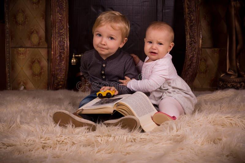Crianças em um tapete macio com livro fotografia de stock