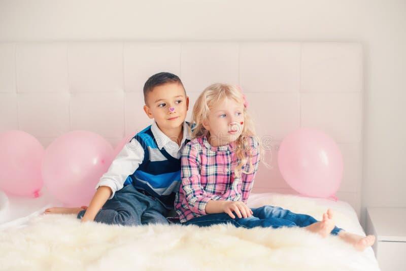 Crianças engraçadas adoráveis bonitos caucasianos com etiquetas do coração em suas caras imagem de stock royalty free