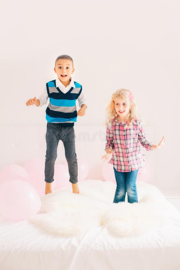 Crianças engraçadas adoráveis bonitos caucasianos que saltam na cama foto de stock