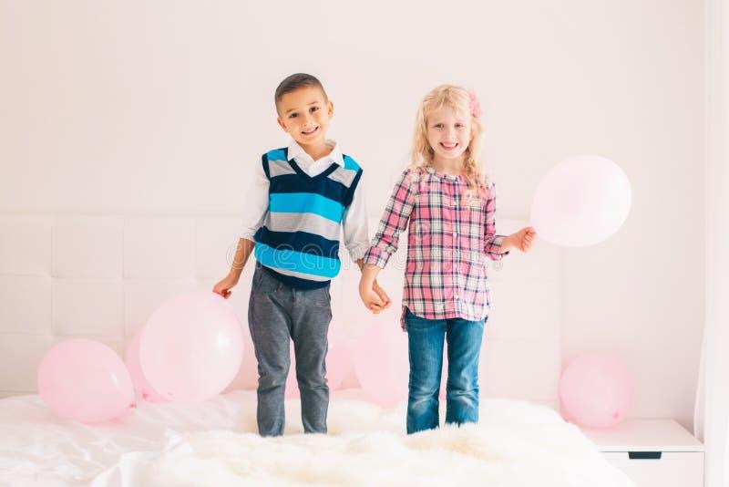 Crianças engraçadas adoráveis bonitos caucasianos que saltam na cama imagem de stock