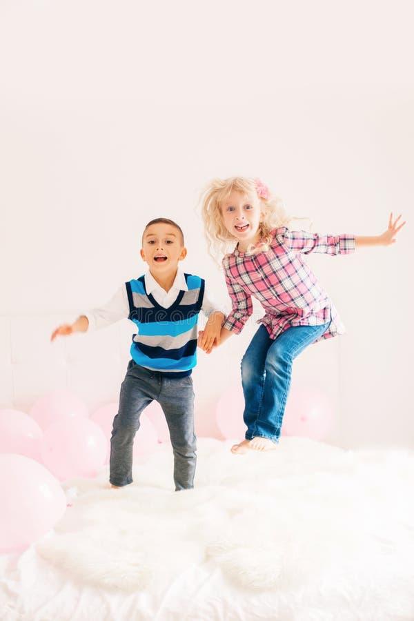 Crianças engraçadas adoráveis bonitos caucasianos que saltam na cama foto de stock royalty free