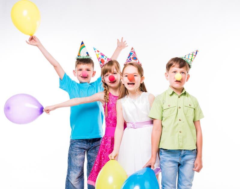 Crianças engraçadas com narizes do palhaço e chapéus do aniversário fotografia de stock royalty free