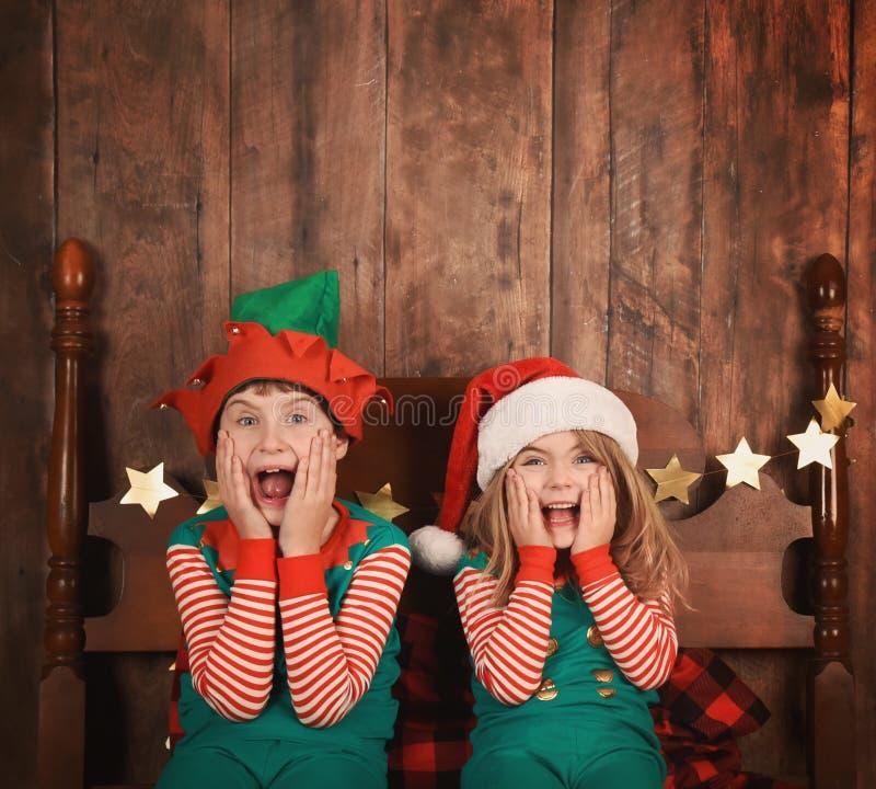 Crianças engraçadas do Natal na cama com chapéus fotos de stock royalty free