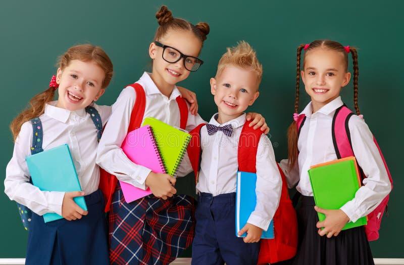 Crianças engraçadas estudante e estudante, menino do estudante e menina do grupo sobre o quadro-negro da escola foto de stock