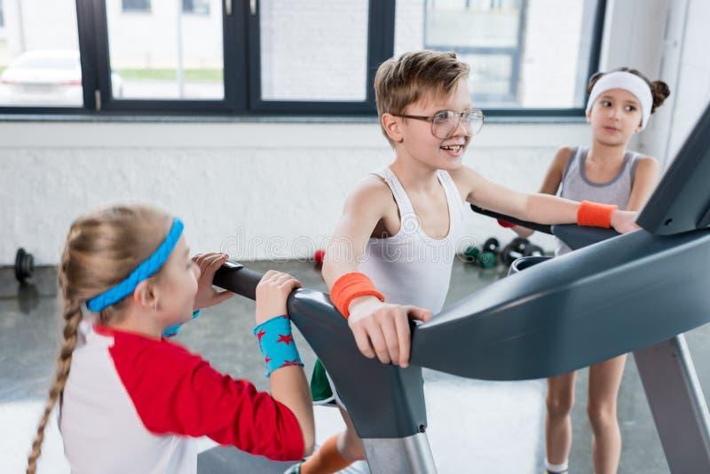 Crianças engraçadas no treinamento do sportswear na escada rolante no gym junto imagem de stock royalty free