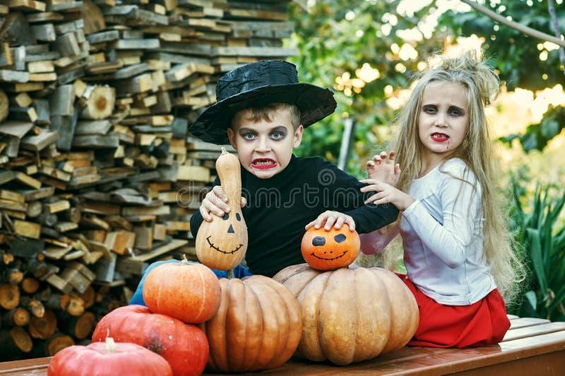 Crianças engraçadas nos trajes com abóboras imagens de stock