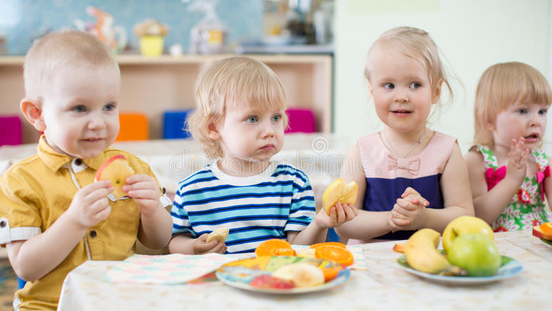 Crianças engraçadas que comem frutos na sala dinning do jardim de infância imagem de stock royalty free