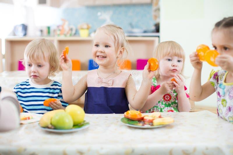 Crianças engraçadas que comem frutos no centro de centro de dia fotos de stock