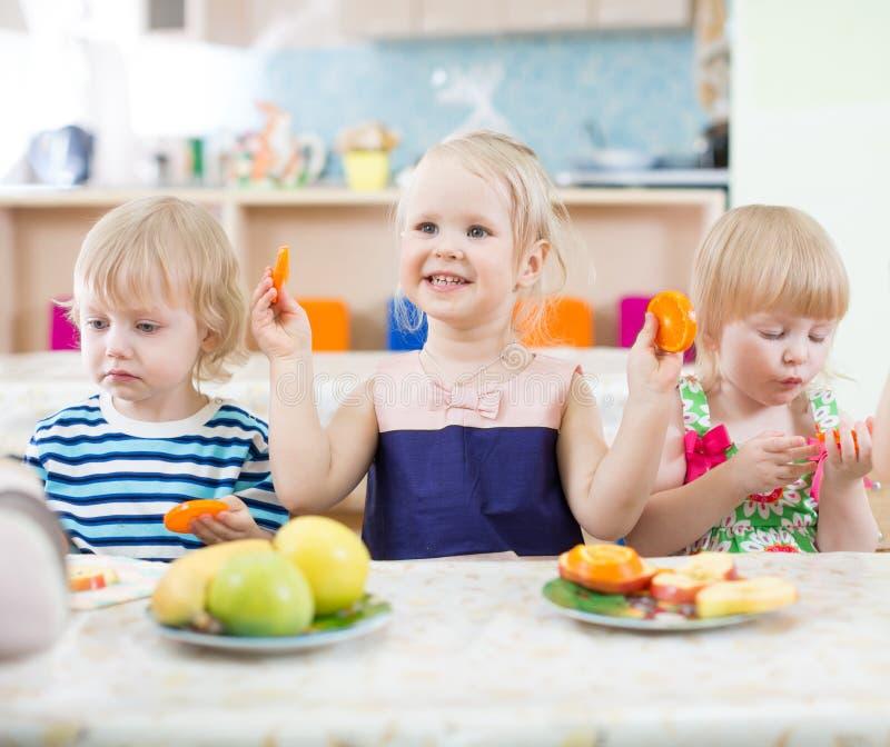 Crianças engraçadas que comem laranjas no centro de centro de dia foto de stock