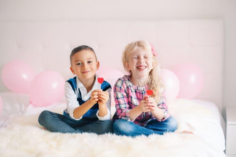 crianças engraçadas que comem pirulitos dados forma coração fotografia de stock