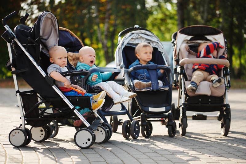 Crianças engraçadas que sentam-se nos carrinhos de criança no parque fotos de stock royalty free