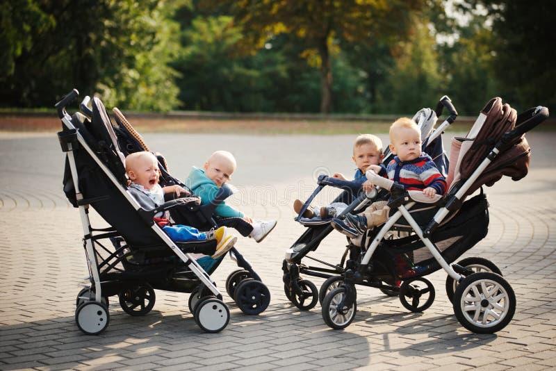 Crianças engraçadas que sentam-se nos carrinhos de criança no parque fotografia de stock royalty free