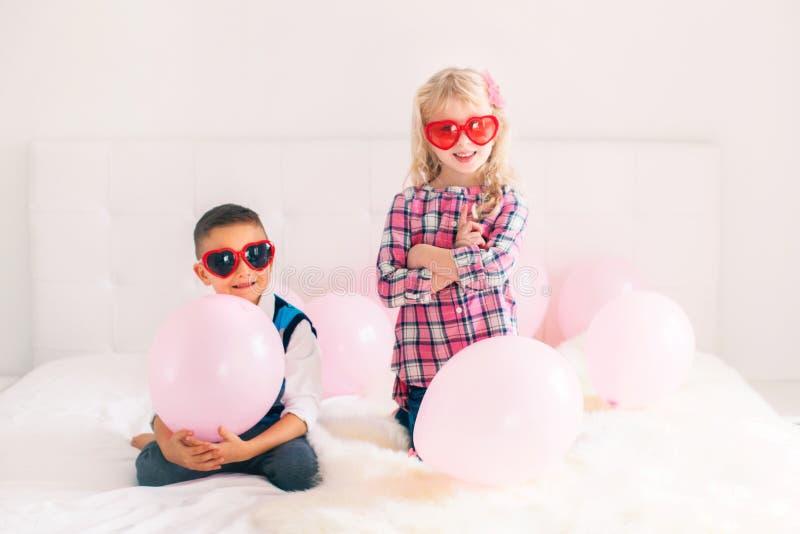 crianças engraçadas que vestem vidros da forma do coração fotos de stock