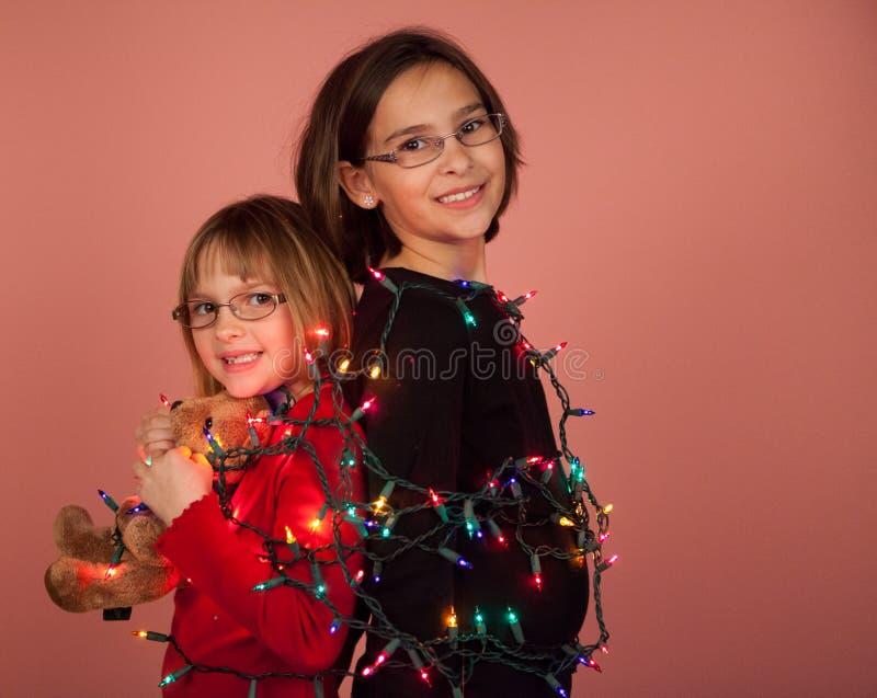 Crianças envolvidas acima em luzes de Natal para os feriados imagens de stock royalty free