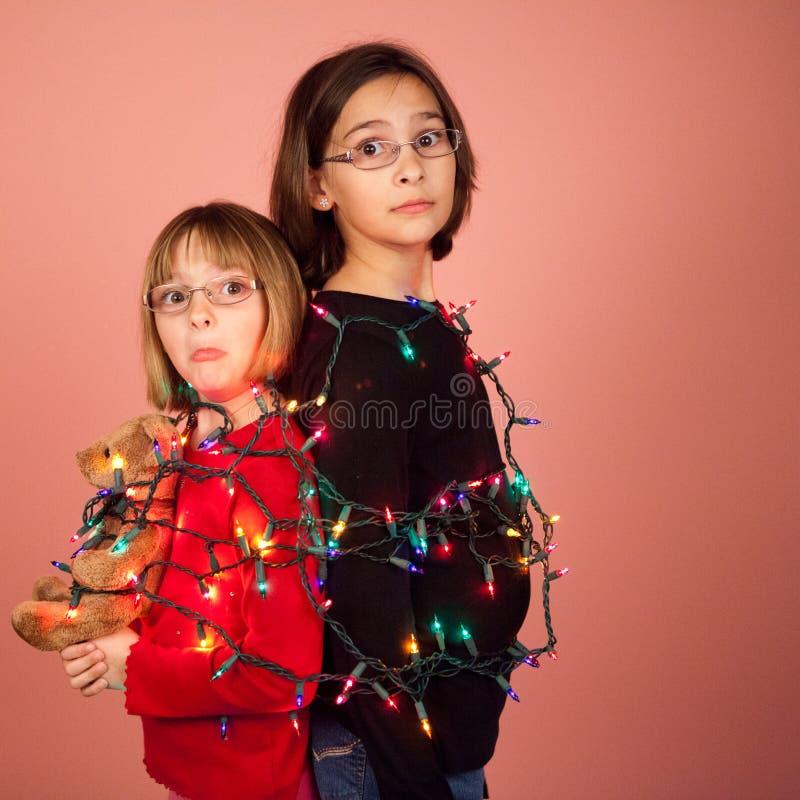 Crianças envolvidas acima em luzes de Natal para os feriados fotografia de stock royalty free