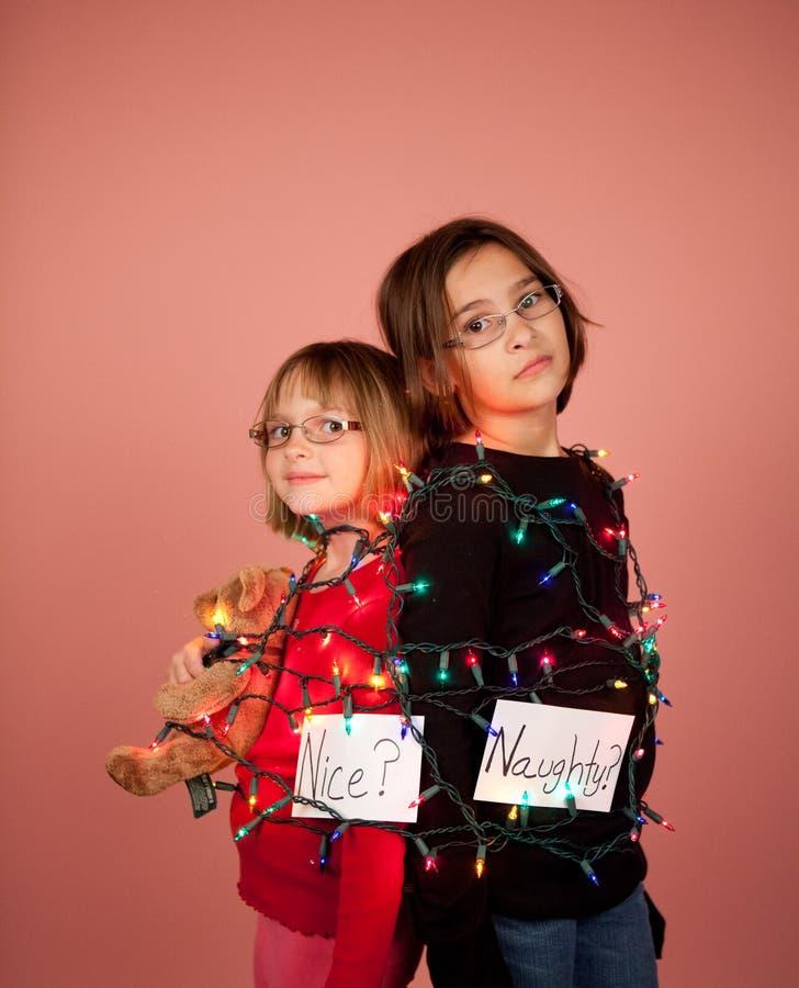 Crianças envolvidas acima em luzes de Natal para os feriados impertinentes e fotografia de stock