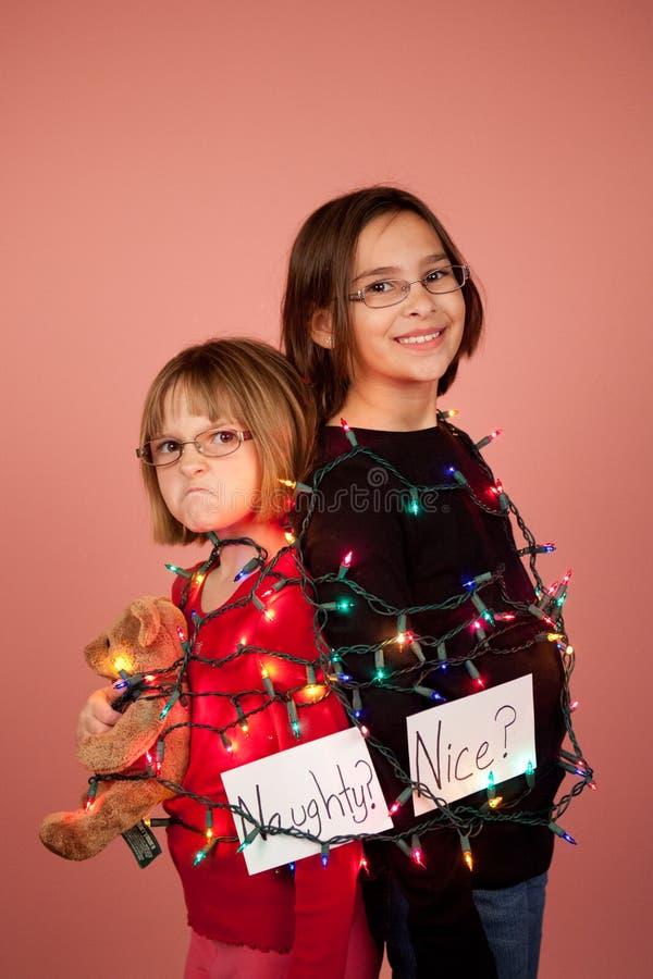 Crianças envolvidas acima em luzes de Natal para os feriados impertinentes e imagem de stock