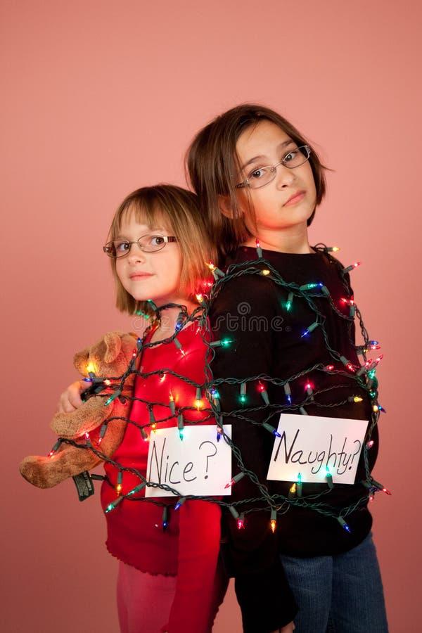 Crianças envolvidas acima em luzes de Natal para os feriados impertinentes e fotos de stock