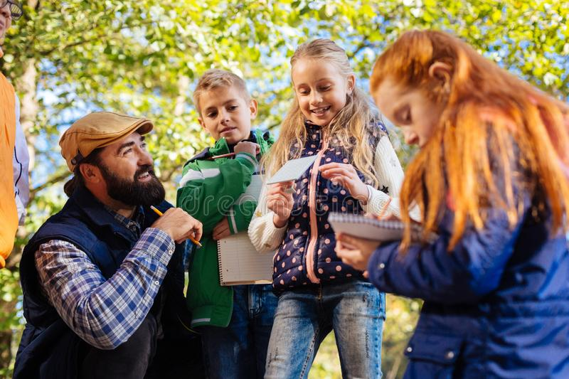 Crianças espertas positivas que apreciam uma lição exterior foto de stock