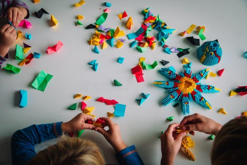 Crianças fazendo artesanato origami com papel, aprendendo imagens de stock