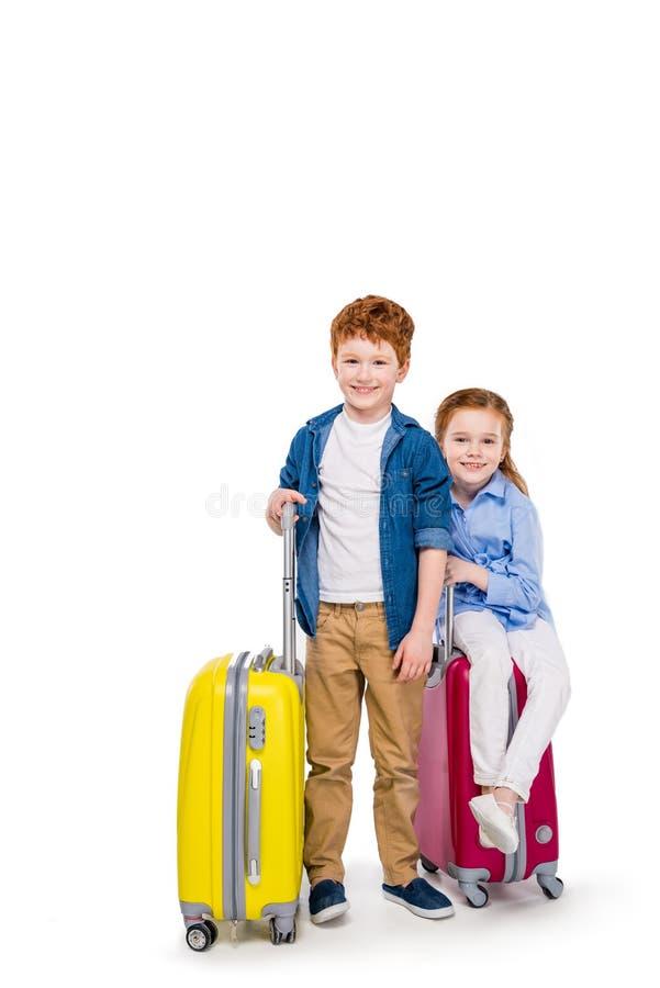 crianças felizes adoráveis do ruivo com malas de viagem que sorriem na câmera imagens de stock