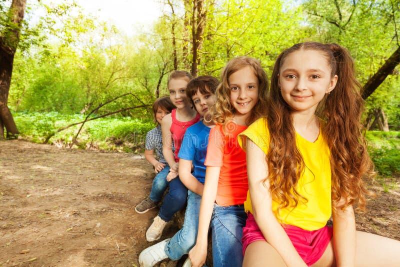 Crianças felizes bonitos que sentam em um início de uma sessão a floresta imagens de stock