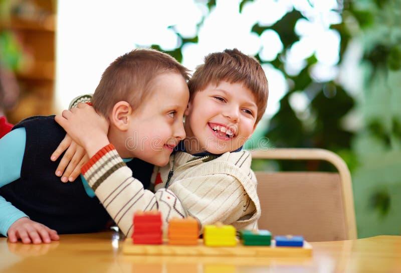 Crianças felizes com inabilidades no pré-escolar fotos de stock