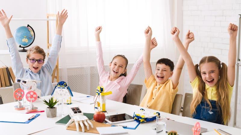 Crianças felizes com mãos levantadas após a classe da robótica fotos de stock