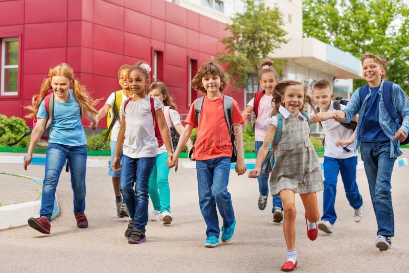 Crianças felizes com mochilas que andam guardando as mãos fotos de stock