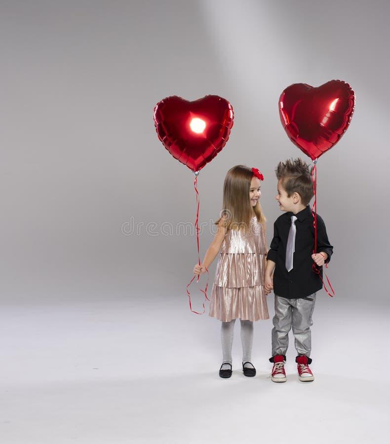 Crianças felizes com o balão vermelho do coração imagem de stock royalty free