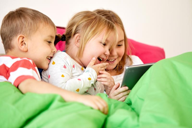 Crianças felizes com o PC da tabuleta na cama em casa fotos de stock