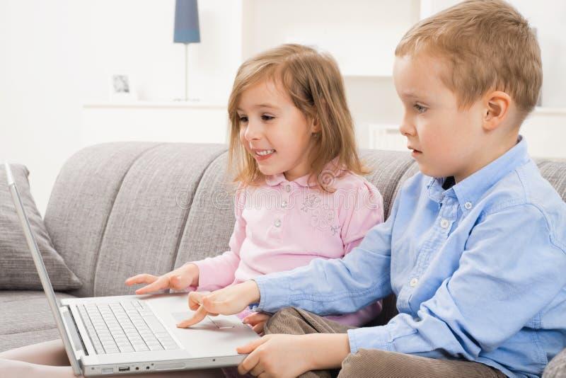 Crianças felizes com portátil fotografia de stock