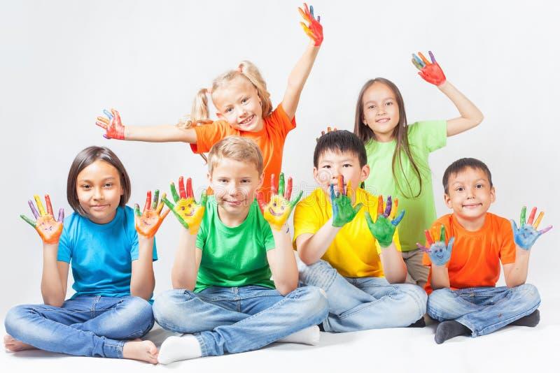 Crianças felizes com sorriso pintado das mãos imagens de stock royalty free