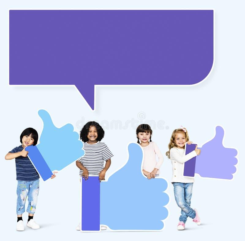 Crianças felizes com uma bolha do discurso que guarda os polegares acima dos ícones fotografia de stock royalty free