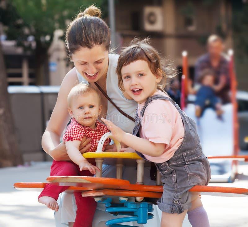 Crianças felizes da mulher em balanços imagem de stock