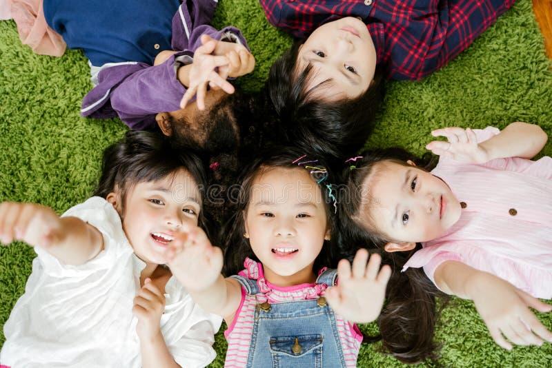 Crianças felizes das crianças que colocam no assoalho de tapete verde da grama na sala de visitas em casa fotos de stock