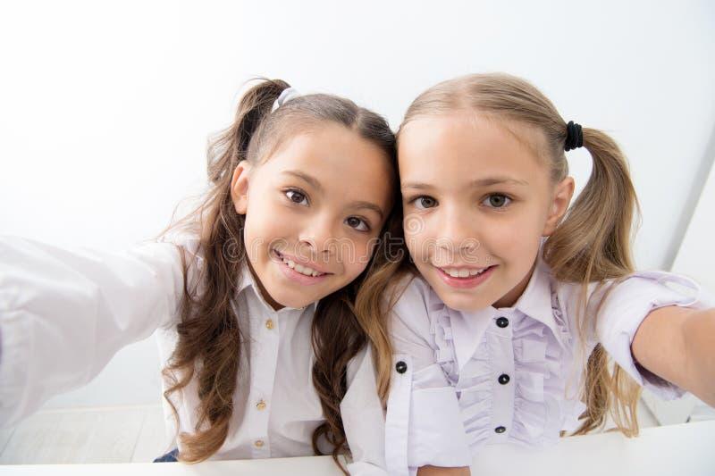 Crianças felizes de volta à escola e ao selfie da fatura selfie de crianças felizes na farda da escola Estudantes alegres conside imagens de stock