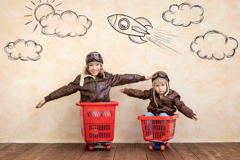 Crianças felizes dirigindo carro de brinquedo em casa fotos de stock royalty free
