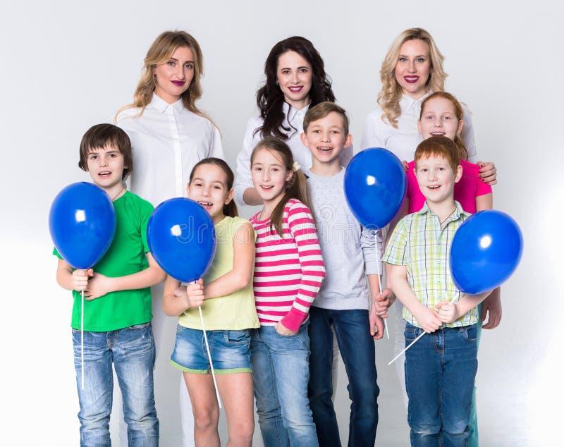 Crianças felizes e adultos que estão no fundo branco, espaço da cópia fotos de stock royalty free