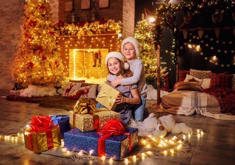 Crianças felizes em chapéus do ` s de Santa com os presentes na sala em Christm imagem de stock