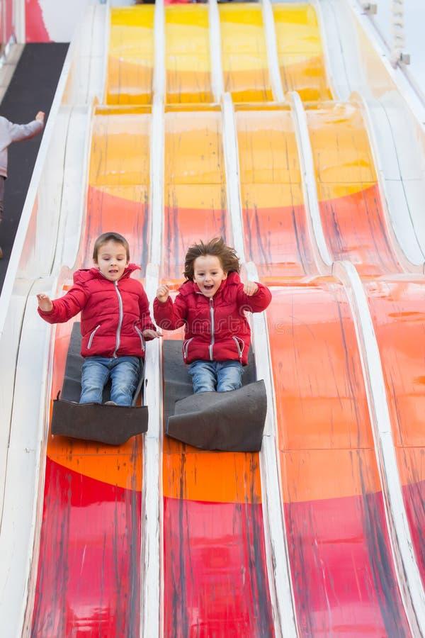 Crianças felizes, indo abaixo da corrediça enorme, feliz, apreciando fotografia de stock royalty free