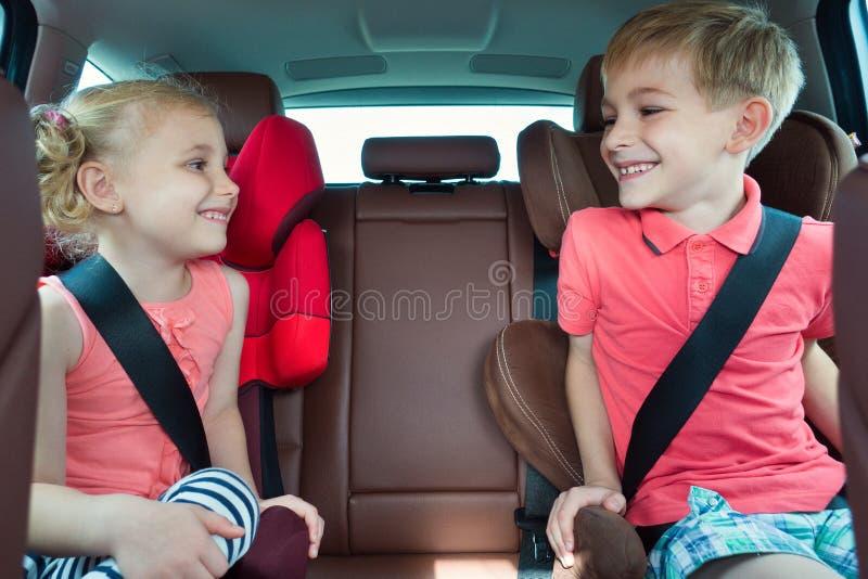 Crianças felizes, menina adorável com seu irmão que senta-se junto em m imagem de stock