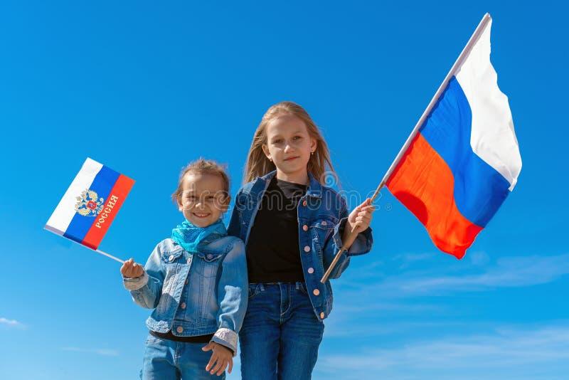 Crianças felizes, meninas bonitos com bandeira de Rússia contra um céu azul claro imagens de stock