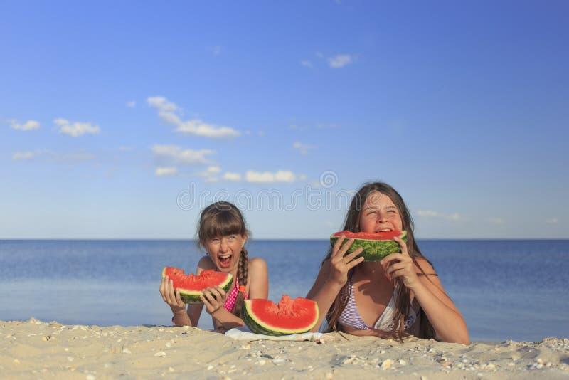 Crianças felizes na praia que comem a melancia doce imagens de stock royalty free