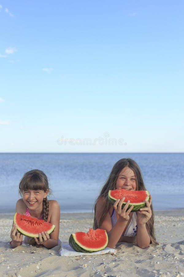 Crianças felizes na praia que comem a melancia doce imagem de stock royalty free