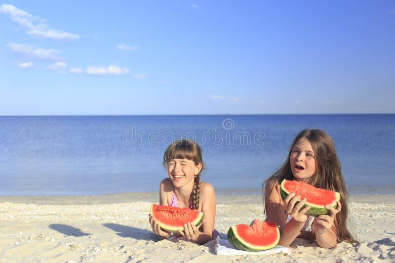 Crianças felizes na praia que comem a melancia doce fotografia de stock