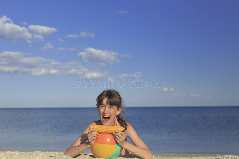 Crianças felizes na praia que comem o milho doce imagem de stock