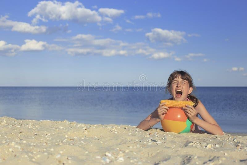 Crianças felizes na praia que comem o milho doce imagens de stock royalty free